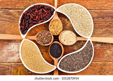 Goji berries, amaranth seeds, chia seeds, kinoa seeds in the ceramic bowls and linen, sesame, kalonji in wooden spoons. Nutritional supplement on wooden background.
