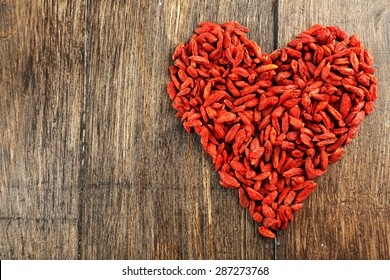 Goji berries arranged in heart shape on wooden background