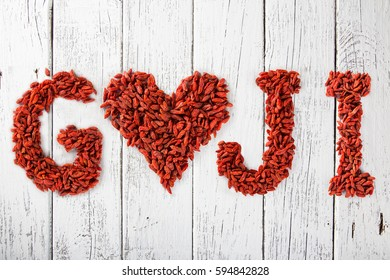 Goji berries as a heart and letters on old white wooden table, top view.
