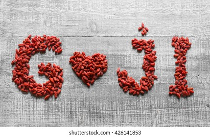 Goji berries shaped as a heart and letters on a white wooden board