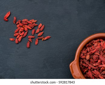 Goji Berries in a small bowl on a slate tablet, shot from above