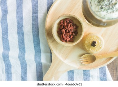 Goji berries in wooden bowl with coffee scone and cold drinks