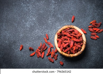 Goji berries in wooden bowl on black background. Top view copy space.