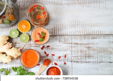 Goji berry juice , jam and smoothie on white wooden background.