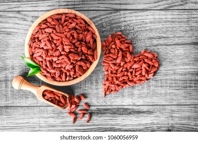 Goji in bowl on wood table. Top view of fresh goji in scoop and bowl. Goji in heart shape on table.