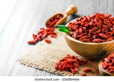 Goji fresh fruits seeds in wooden bowl with scoop ful of goji. Goji on table.