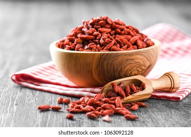 Goji fresh fruits in wooden bowl on rustic table. Red goji fruits with wood scoop.
