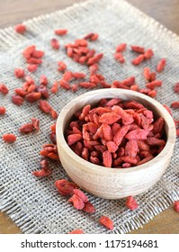 Goji in wooden cup place on sackcloth.