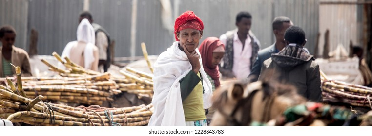 GOJO, ETHIOPIA-OCTOBER 28, 2017: An unidentified woman stands in a market full of sugarcane in rural Gojo, Ethiopia.