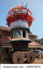 GOKARNA, INDIA - JANUARY 31, 2014: The ancient  wooden chariots with flags and paintings of hindu gods in the sacred village Gokarna