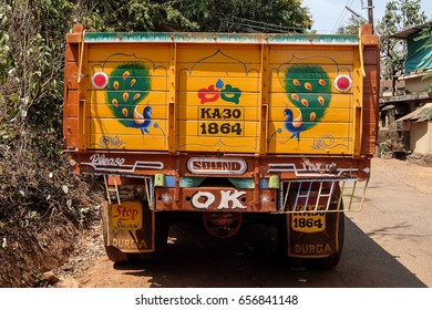 Gokarna, India - March, 1st, 2017. Colorful cargo truck under a summer blue sky with rich decorative paintings, typical for the trucks in India.