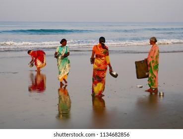 Gokarna, Karnataka, India - January, 19, 2018. Fishermen's wives wash the pots from their morning meal near a small fishing camp on the main beach at Gokarna.