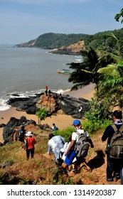 Gokarna, Karnataka, India - November 11, 2017. Trekkers descend a cliff and arrive on a beautiful rocky beach near Gokarna, a town famous for beaches.