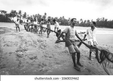 Gokarna, Karnataka India - October 09 2016: Fishermen of Gokarna go into some troubled waters with smiles at Gokarna beach on a rainy overcast day. Group of men Fishing with nets on the beach
