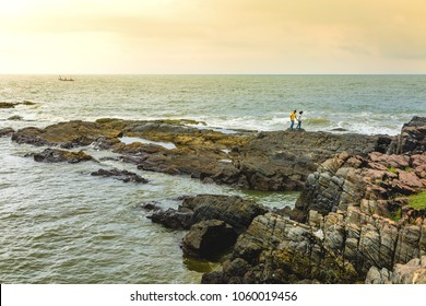 Gokarna, Karnataka India - October 10 2016: An unidentified couple take  a walk on the rocky cliff of Om beach in Gokarna, Karnataka, India at sunset. Aum/Om shaped beach . Boat passing at Horizon