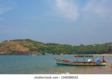 Gokarna, Karnataka/India - 24.11.2018: large colored pleasure boat with a canopy near the sandy shore against the background of the beach and the hill with green trees