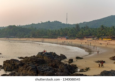 Gokarna, Karnataka/India - 26.11.2018: rocks in the sea near the sandy beach with people resting and swimming on the background of huts and green palm trees