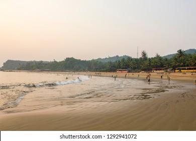 Gokarna, Karnataka/India - 26.11.2018: Sea sandy beach against the backdrop of people swiming and the green jungle in the evening