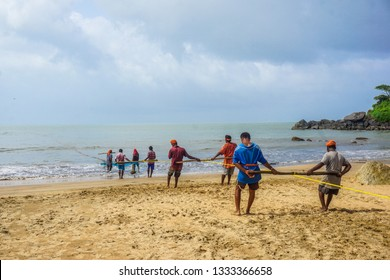 Gokarna Village, Karnataka State, India - July 31, 2017: Indian men catch fish using a long net. Several people are pulling the net at once, as it is very hard.