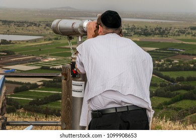 Golan Heights, Israel - May 6, 2018 : Religious jew man observing the Israeli Syrian border with binoculars in Golan Heights, Israel