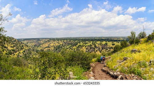 Golan heights natural reserve. Israel. Backpackers walking the dirt track.