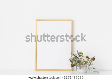 3acac58ad0af Gold a4 portrait frame mockup with dried field wild flowers in small white  poton white wall