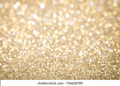Gold Abstract Christmas twinkled bright background with bokeh defocused lights . Lights Festive background concept.