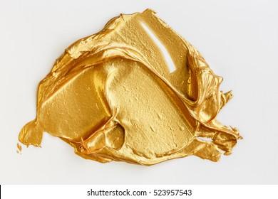 Gold acrylic paint on white background