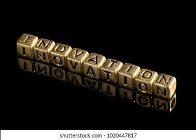 """Gold alphabet block Lay stack the word """"INOVATION"""" on black background."""