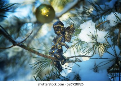 Gold  angel  on a fir-tree branch in the snow-covered wood. Christmas background