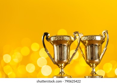 Gold award trophy against bright yellow background with blurred lights