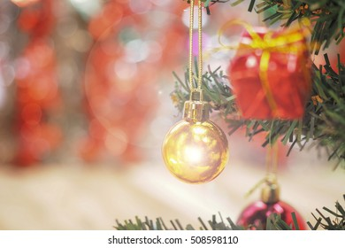 Gold ball christmas ornaments on tree and color lights at the background