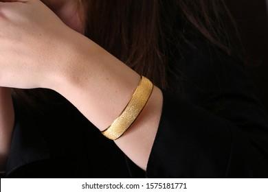 Gold bangle on young woman hand