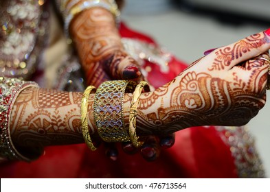 gold bangles in hand, graceful poses of girls hand wearing gold bangles, designer gold bangles and hand, girls hands with golden bangles, closeup,