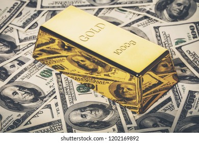gold bar close-up on the background of hundred dollar bills