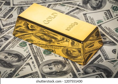 gold bar close-up on background of hundred dollar bills