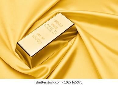 Gold bar on satin fabric. financial concept.