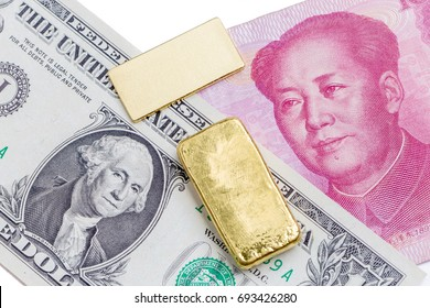 Gold bar over the US dollar bill and Chinese yuan banknote on white background, economy finance concept.
