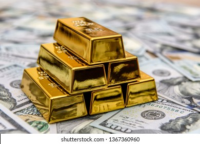 Gold bars with hundred dollar banknotes as background