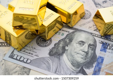 Gold bars on US dollar bill banknotes background. Concept of gold future trading, online asset commodity trading or buy gold bars for investment. It has been valued as a global currency, a commodity.