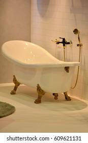 Gold bathtub with golden faucet. Luxury bathroom. Vintage bathtub. Posh bathroom