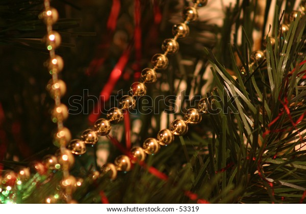 gold beads on a green christmas tree with red strands of tinsel