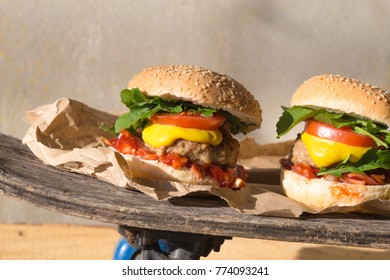 Gold beef burger with arugula and cheese and ketchup s on a rustic wooden table
