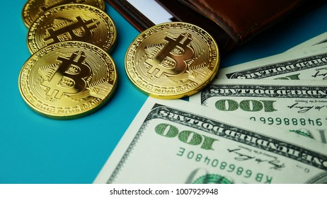 Gold Bitcoin BTC coins with brown wallet and bills of 100 dollars. Worldwide virtual internet cryptocurrency Digital coin money and digital payment system on bitcoin farm in cyberspace