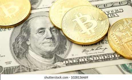 Gold Bitcoin BTC coins falling on bills of 100 dollars. Bitcoin coin gold virtual currency