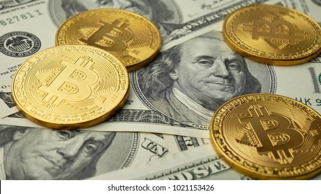 Gold Bitcoin BTC coins rotating on bills of 100 dollars