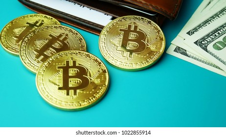 Gold Bitcoin BTC coins rotating with brown wallet and bills of 100 dollars. Worldwide virtual internet cryptocurrency Digital coin money and digital payment system on bitcoin farm in cyberspace