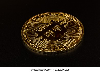 Gold bitcoin in close-up on black background. Business, money, cryptocurrency concept.