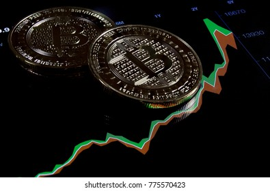 Gold Bitcoin coin laying on market chart black background