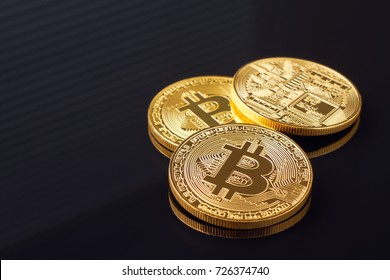 Gold bitcoin coin stacked against a dark background close-up. Bitcoin cryptocurrency